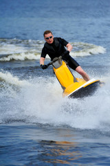 Young man riding jet ski