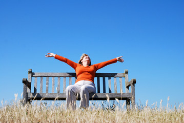 Ecstatic woman sitting on bench