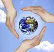 schützende Hände um den Planeten Erde