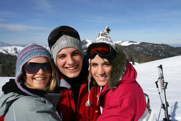 Jeune homme entouré de deux jeunes femmes à la neige