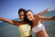 Jeunes femmes souriantes au bord de la plage levant les bras