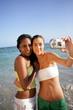 Jeunes femmes se photographiant au bord de la plage