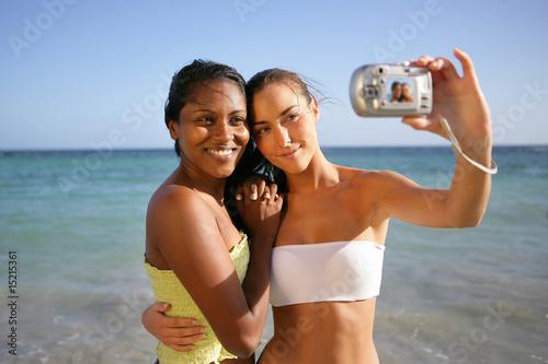 Jeunes femmes souriantes au bord de la plage se photographiant