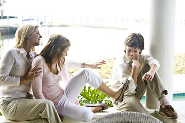 Family on terrace, teenager girl teasing younger brother