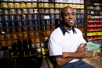 Man sitting in front of colored inks in print shop