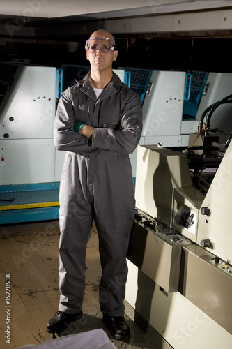 Man in print shop standing by printing press
