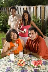 Interracial family in backyard having refreshments