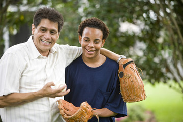 Interracial father and teenager in backyard with baseball gloves
