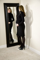 Pregnant woman admiring her shape in a mirror