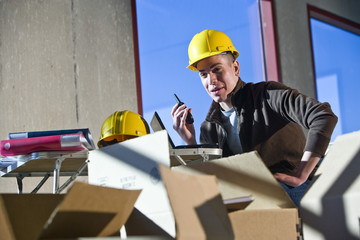 Construction worker in unfinished room surrounded by boxes