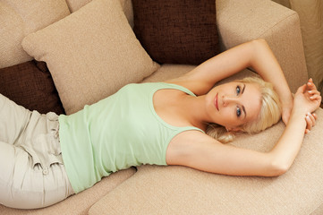 Beautiful young woman relaxing on a sofa....