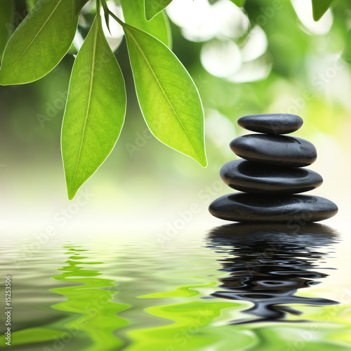 Leinwandbild Motiv Zen stones pyramid on water surface, green leaves over it