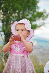 A little girl drinking from bottle outdoor