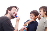 Father teaching his two sons how to clean the teeth poster