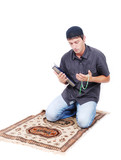 Muslim man is holding holly book Qoran and praying on traditiona poster