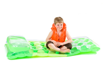 Boy sitting on beach mattress