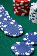 Poker chips spread out over a green surface.