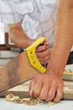 a joiner sawing a plank poster