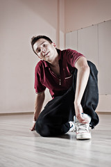 handsome breakdancer sitting on the floor