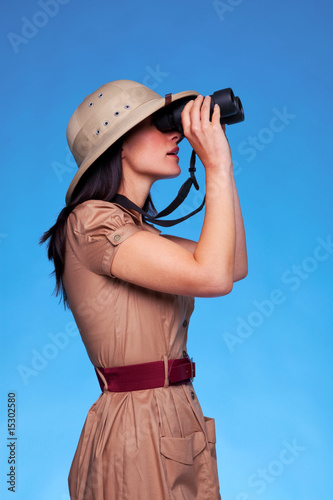 Woman in safari hat looking through binoculars side view
