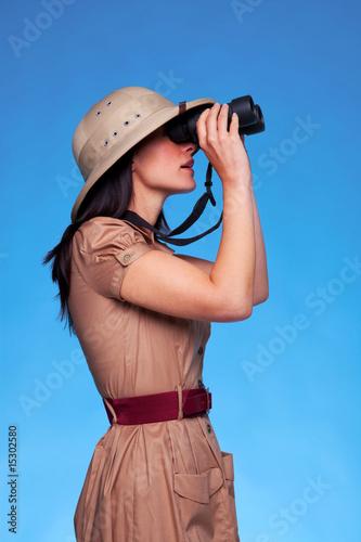 Woman in safari hat looking through binoculars side view