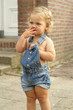 Cute 2 year old girl is standing outside