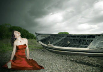 woman and a boat under a stormy sky