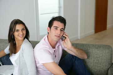 homme téléphonant assis près d'une femme souriante