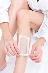 depilation on the female legs with waxing