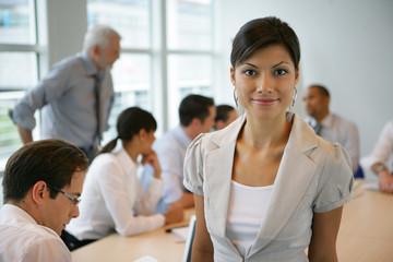 Femme métisse devant un groupe de personnes en formation