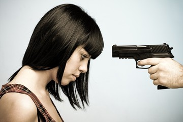 Innocent victim. Young beautiful woman and gun.