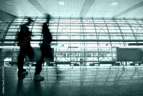 people rushing in airport , blue tone