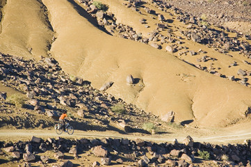A woman Cycling in the desertic Draa Valley, Morocco