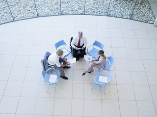 Aerial view of three office workers meeting in a rotunda