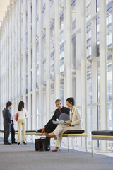 Businessman and businesswoman sitting on bench in corridor with document