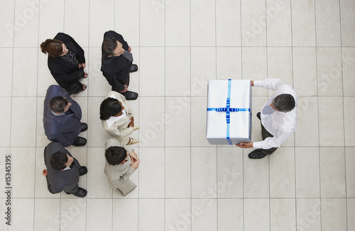 Aerial view of businessman presenting group of businesspeople with gift box