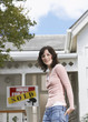 Woman standing in front of house with sold sign