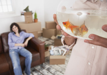 Man holding goldfish bowl with woman on sofa and cardboard boxes