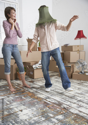 Woman and man with lamp shade on head in home with cardboard boxes