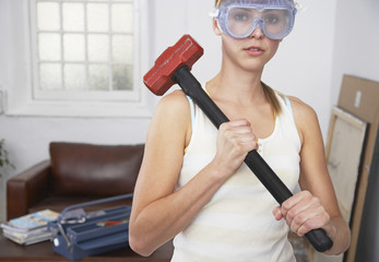 Woman with mallet and eye goggles at home
