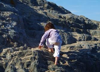 enfant qui escalade des rochers pieds nus