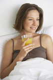 Woman in bed with glass of orange juice