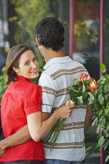 Man and woman outdoors with flowers embracing