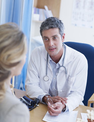 Male doctor talking to woman