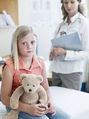 Girl with teddy bear and female doctor