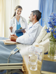 Female doctor or nurse in hospital with male patient