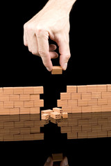 hand putting bricks on a broken wall isolated on black
