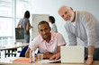 Hommes souriants au bureau avec documents devant un ordinateur