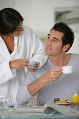 Homme et femme se regardant en prenant leur petit déjeuner