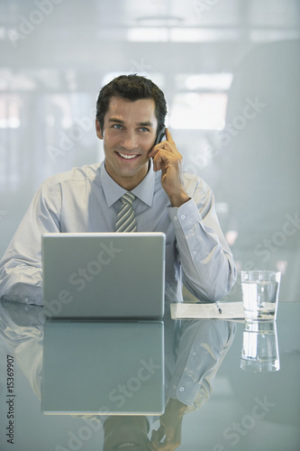 Businessman with laptop and glass of water talking on cell phone